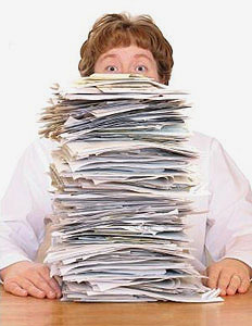 A great big pile of invoices that nearly towers over a woman. Don't let your paper invoices take over your finance department. Every financial throughout the UK can benefit from out invoice scanning services